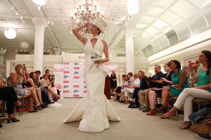 High-profile wedding planner and host of ÒMikie Saves the DateÓ, Michael Russo, poses with the winning dresses of the 11th Annual Toilet Paper Wedding Dress Contest presented by Cheap Chic Weddings and Charmin on Wednesday, June 17, 2015 in New York. (Amy Sussman/AP Images for Charmin)
