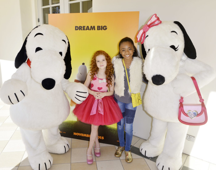 """Snoopy and his fashionista sister Belle joined Francesca and Skai Jackson from Disney's """"Jessie"""" for a shot in front of the new Peanuts Movie poster displayed at the party."""