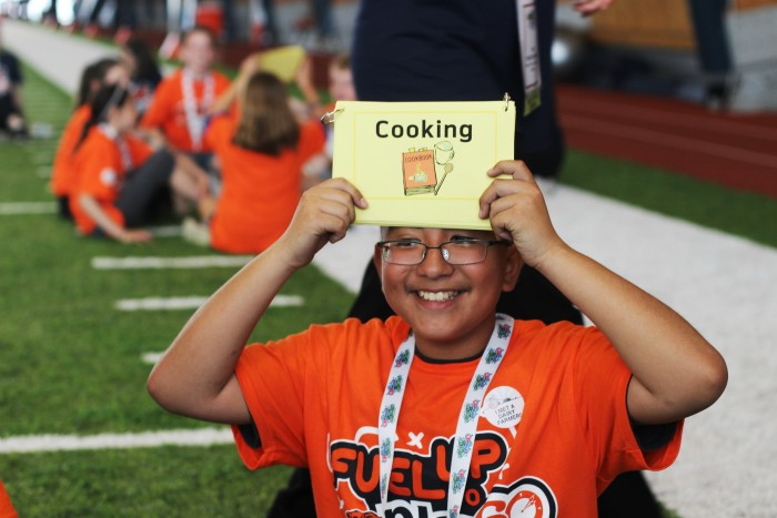 Student holding a sign up that says cooking